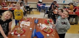 Mrs. Porter's class building gingerbread houses.
